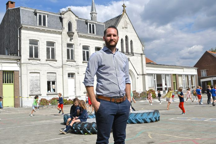 Directeur Maxim Esprit met op de achtergrond de  oude schoolgebouwen die straks verdwijnen.
