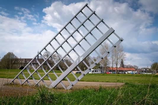Een van de twee halve wieken die uit de grond komen bij het kunstwerk De Verzonken Molen.