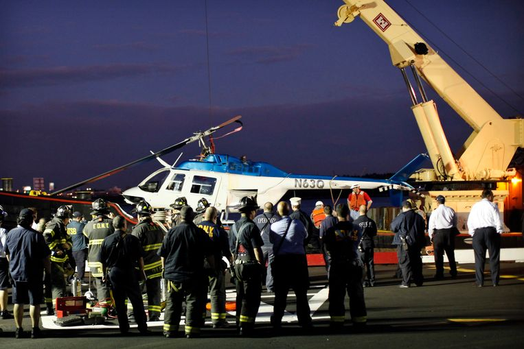 Search and rescue team member watch after a helicopter was pulled out from the water after crashed in the East River with five people aboard after taking off from the 34th street helipad in New York October 4, 2011. A helicopter with tourists aboard crashed into New York City's East River on Tuesday, killing one person and injuring four others, police said.  REUTERS/Kena Betancur (UNITED STATES - Tags: DISASTER TRANSPORT) Beeld REUTERS