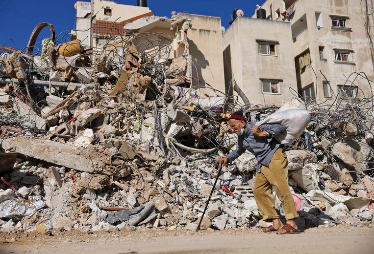 Een Palestijnse man loopt langs een verwoest pand in Gaza.  Beeld AFP