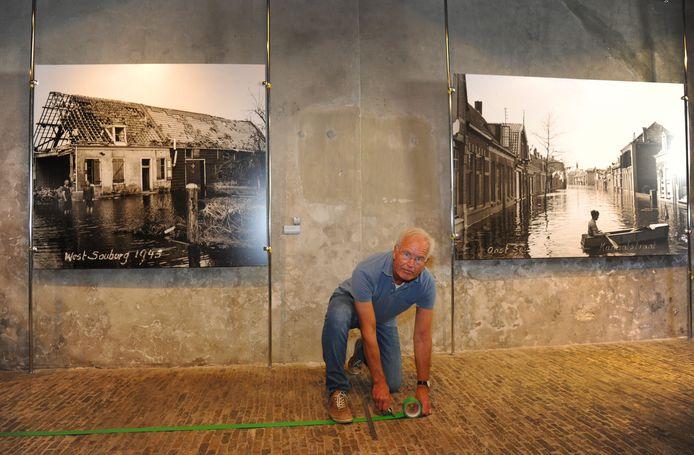 François Hulsbergen, vrijwilliger van het muZEEum in Vlissingen, brengt groene tape aan om de looproute aan te geven.
