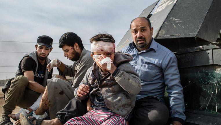 Mannen van het Iraakse leger helpen gewonde burgers in het noordoosten van Mosul. Beeld null