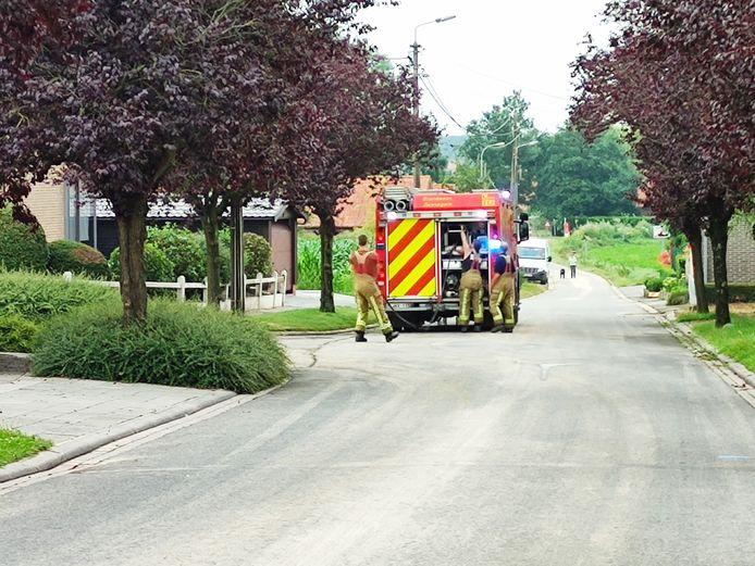 De brandweer ruimt modder op de weg in Sint-Denijs