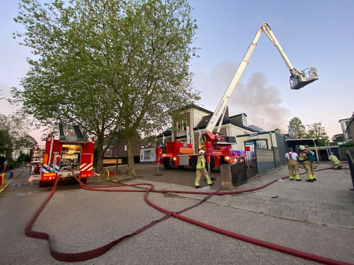 Met een hoogwerker probeert de brandweer de vlammen te blussen