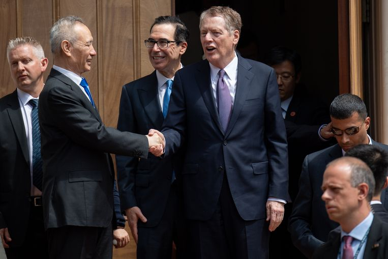 De Chinese vice-premier Liu He schudt de hand met de Amerikaanse onderhandelaar Robert Lighthizer. Beeld AFP
