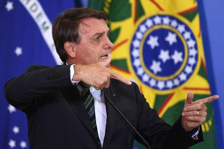 De Braziliaanse president Jair Bolsonaro maakt het schietgebaar waarmee hij regelmatig zijn wens om ruimere wapenwetten kracht bijzet. Beeld AFP