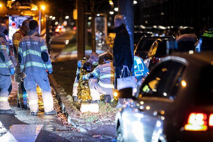De gewonde voetgangster krijgt eerste hulp van de brandweer die bij toeval bij het ongeval op de Huissensestraat in Arnhem uitkwam.