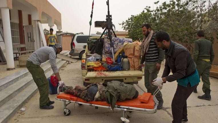 Een slachtoffer van de Navo-luchtaanval wordt door rebellen afgevoerd. Beeld AFP