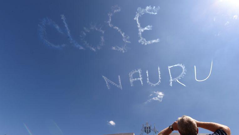 Een protest vanuit de lucht boven het regeringsgebouw in Canberra, Australië, tegen het gebruik van het eiland Nauru als detentiecentrum voor vluchtelingen. Beeld EPA