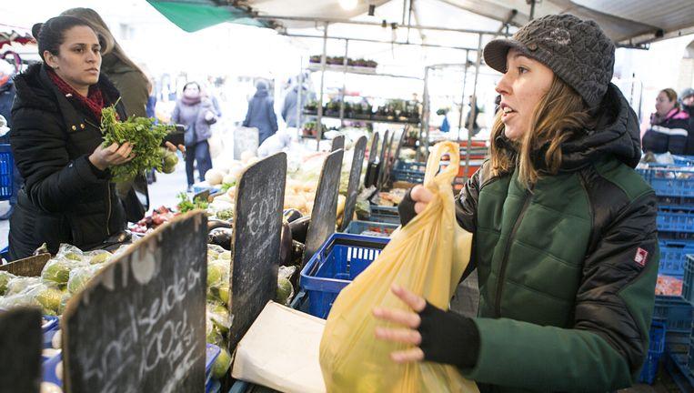 Klanten krijgen nu nog een plastic zak mee op de Amsterdamse Ten Katemarkt. Vanaf volgend jaar is dat verboden. Beeld Julius Schrank
