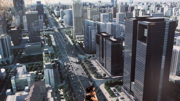 Vrouw loopt langs reclame in Peking. Beeld EPA
