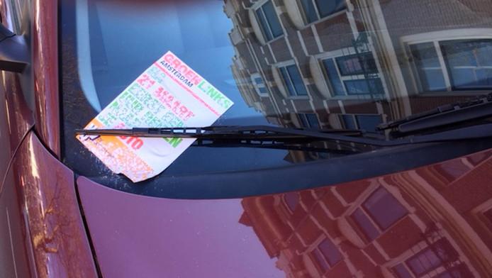 Een vastgeplakte flyer op een auto op de Eerste Helmerstraat