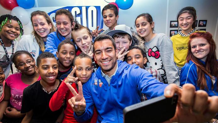 Giovanni van Bronckhorst als trainer van SV Gio te midden van de deelnemende kinderen.