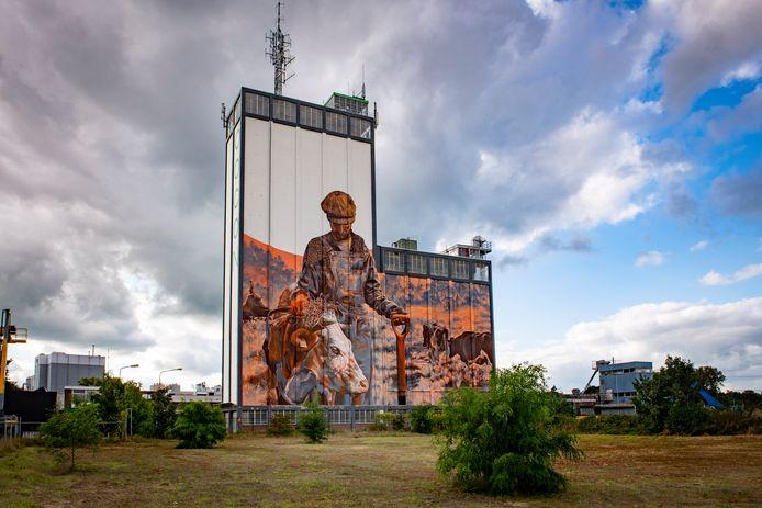 Kunstenaar Miel Krutzmann legt morgen de laatste hand aan zijn enorme muurschildering op 50 meter hoge silo van Op- en Overslag Coöperatie Oost Nederland in Lochem.