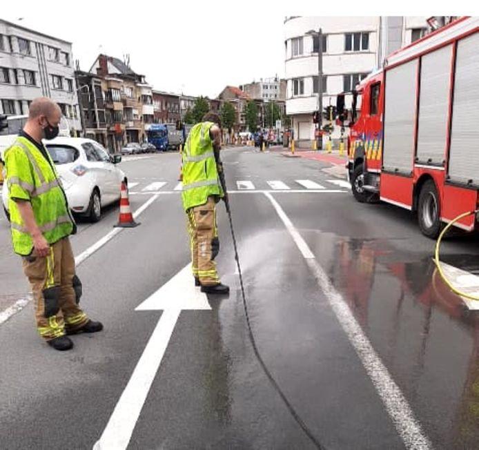 De brandweer reinigt het wegdek met hogedrukreinigers.