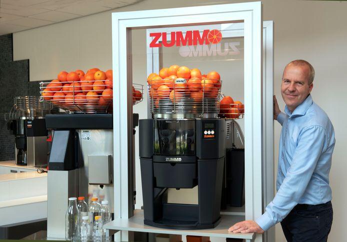 Martin van Rossum van Woertman bij een sinaasappelpers, een van de apparaten die zijn bedrijf verkoopt.