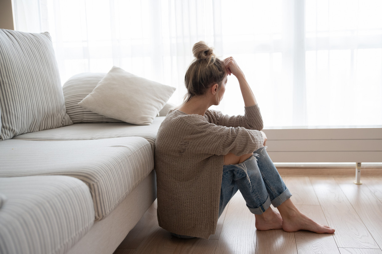 A depressed woman is sitting on the floor in the living room. Beeld Shutterstock