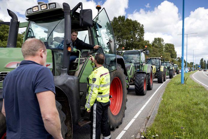 FDF-voorman Thijs Wieggers (in de tractor) in gesprek met een agent. De boeren verzamelden zich vrijdag in Zoetermeer om actie te gaan voeren bij supermarktbranchevereniging CBL in Leidschendam. Na het protest werd Wieggers opgepakt in Bleiswijk.
