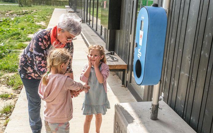 Carine Penet met kleinkinderen Félice en Lucie, bij een SMOT-spot in speeldomein De Warande in Heule