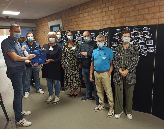 Burgemeester Tony Vermeire overhandigt een koeltas aan de vrijwilligers naast de fotomuur.