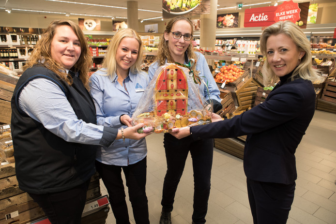 Cindy Haye, Laura ten Bolscher en Martine Woolderink (van links naar rechts) krijgen uit handen van Anne Demmer het eerste exemplaar van de Sinterklaas-aftelkalender.
