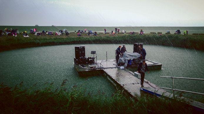 Een zomerbui overvalt de deelnemers aan een sing-in op de 'dobbe' (vijver).