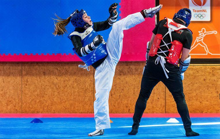 Taekwondoka Bodine Schoenmakers (gewichtsklasse onder 57 kg) trapt in de richting van het hoofd van haar training Giorgi Janmaat. Schoenmakers is 13 keer kampioen van Nederland geworden. Via crowdfunding probeert Bodine geld op te halen om te kunnen meedoen aan de Zomerspelen. Nog 137 dagen tot Tokio. Beeld Klaas Jan van der Weij