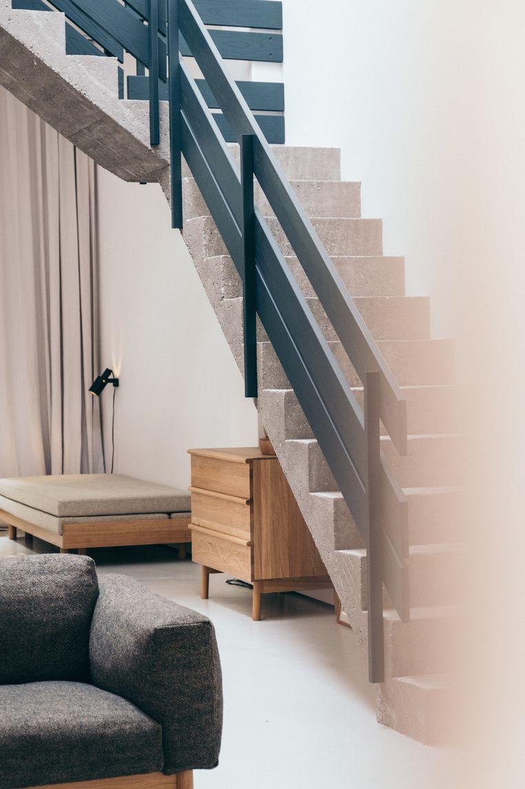 In de showroom zie je de zetel, het ladekastje en het daybed van haar eigen merk. Het zwarte  wandlampje Nomad is van het Zweedse merk Rubn. De betonnen trap is een van de ingrepen van Marina in de ruimte. Beeld null