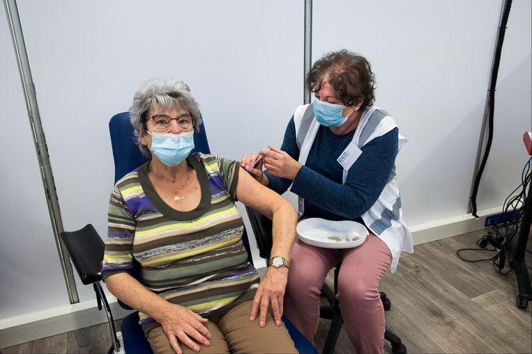 Een vrouw in Leiden wordt gevaccineerd door een vrijwilliger van het Rode Kruis. Beeld Arie Kievit