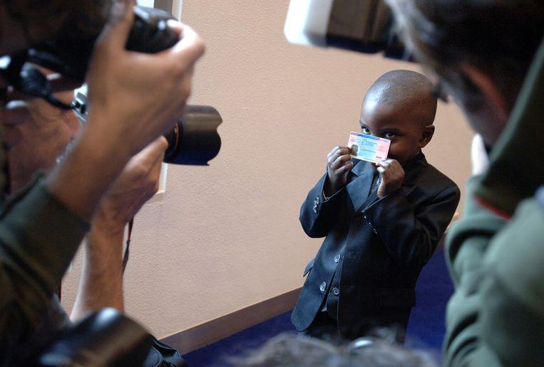 De 4-jarige Dieuci Zawali toont in juli 2017 zijn verblijfsdocument aan de media. Zijn familie kreeg als eerste een verblijfsvergunning in het kader van de pardonregeling van toen. Beeld Marcel van den Bergh / de Volkskrant