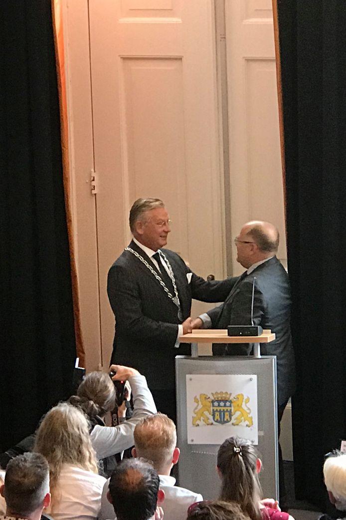 Plaatsvervangend voorzitter van de gemeenteraad Kees Metz heeft zojuist de ambtsketen bij nieuwe burgemeester Pieter van Maaren omgehangen.