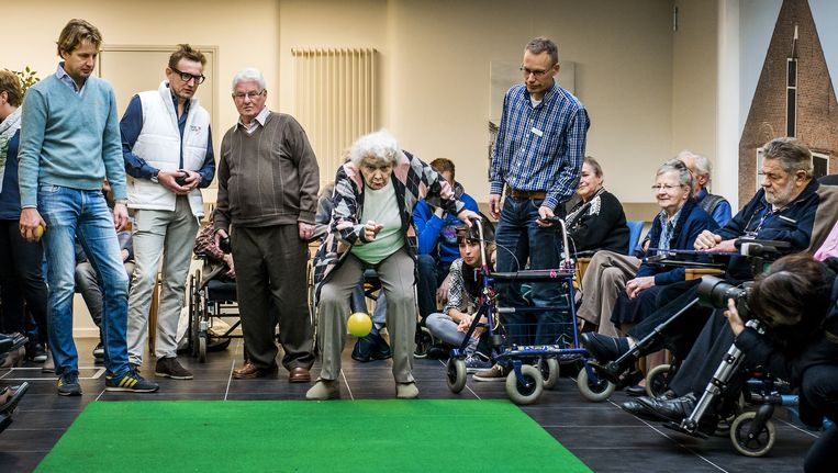 Prins Floris (L) en prins Bernhard kijken naar een potje koersballen in verpleeghuis Norschoten tijdens de nationale vrijwilligersactie. Beeld ANP