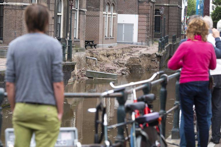 Mensen bekijken de meest recente ingestorte kademuur in Amsterdam, langs de Grimburgwal. Tientallen kilometers kademuur in het centrum verkeren in slechte staat door jarenlange verwaarlozing.  Beeld ANP