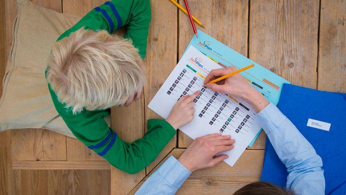 Een jeugdhulpverlener helpt een jongen met zijn dagschema.