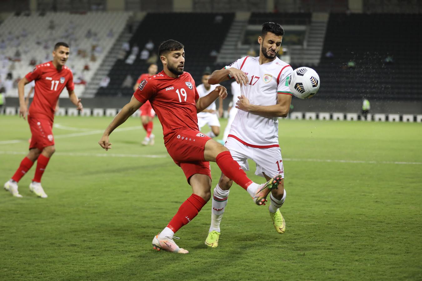 Omid Popalzay (links) tijdens de wedstrijd tegen Oman, waarin hij scoorde met een fraaie volley.