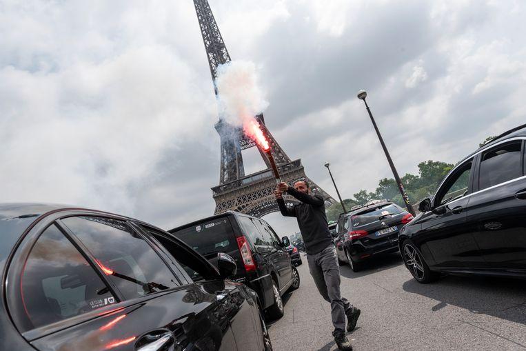 Een taxichauffeur loopt rond met vuurwerk terwijl tientallen taxi's het verkeer aan de voet van de Eiffeltoren blokkeren tijdens een protest tegen de huidige LOM-wet die oneerlijke concurrentie door bedrijven als Uber zou versterken. Beeld NurPhoto via Getty Images