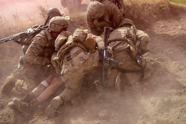 2012: Amerikaanse soldaten beschermen een gewonde kameraad tegen zand en rook nadat ze tijdens een patrouille in de Afghaanse provincie Logar door een bermbom zijn getroffen.   Beeld Munir Uz Zaman / AFP