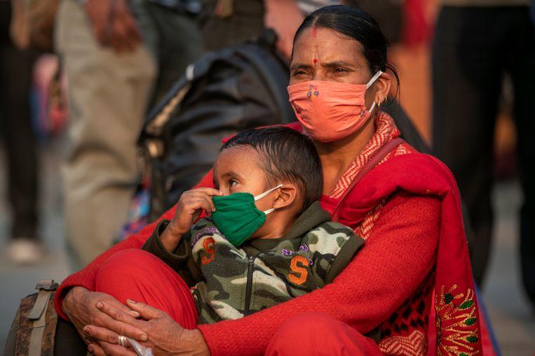 Een vrouw met haar kind bij het busstation van Kathmandu. Beeld AP