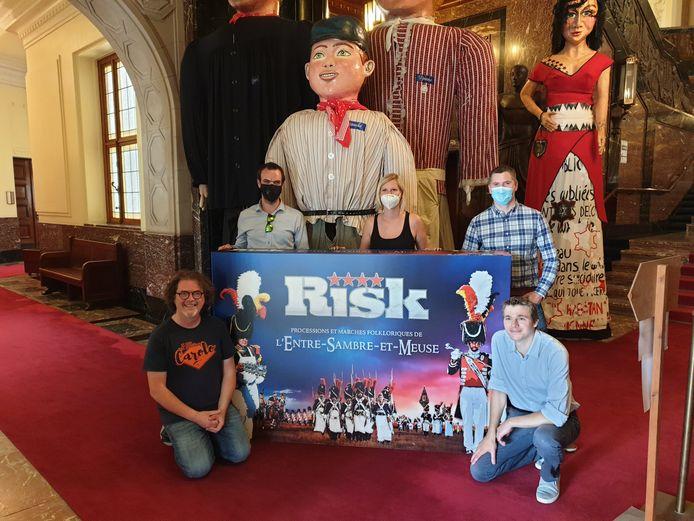 Les concepteurs du jeu Risk sur les marches de l'Entre-Sambre-et-Meuse, le directeur artistique de Dico Games et l'échevine du Folklore de la Ville de Charleroi, Babette Jandrain (PS)
