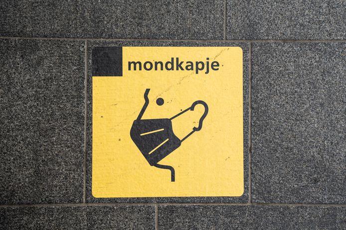 Tegel met mondkapjes symbool op Arnhem centraal.