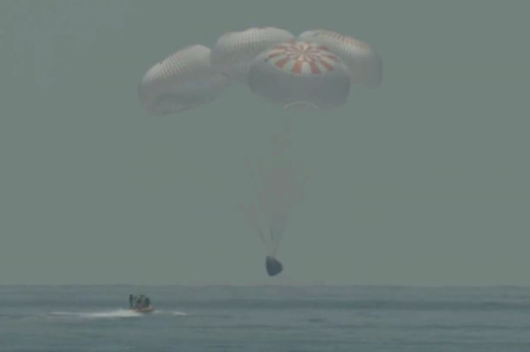 De capsule van SpaceX net voordat hij in zee plonst. Beeld AP