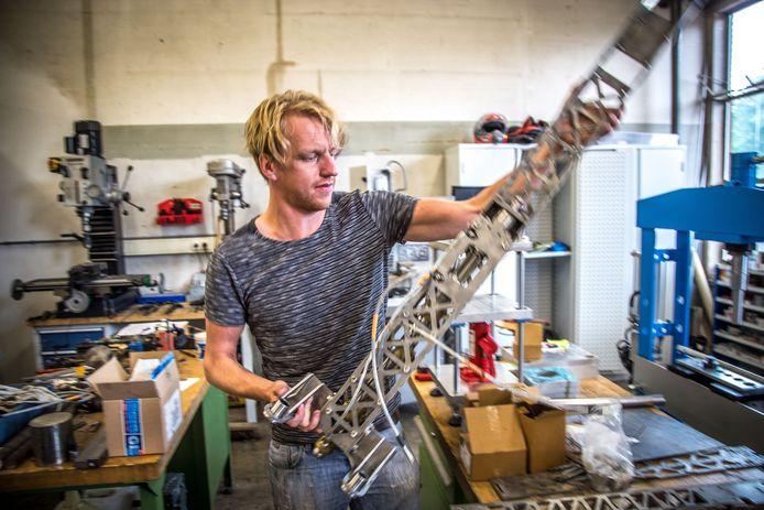 Peter Bas Schelling met de machine die muntjes gaat maken op het Stadsfestival van gerecycled plastic.