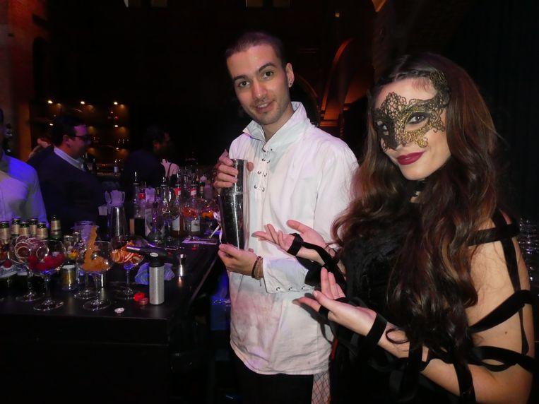 """Cocktailshaker Vincent van den Brink en actrice Mariella Kaveo, die mensen in de zaal aanspreekt: """"We hebben vier soorten cocktails."""" Beeld Hans van der Beek"""