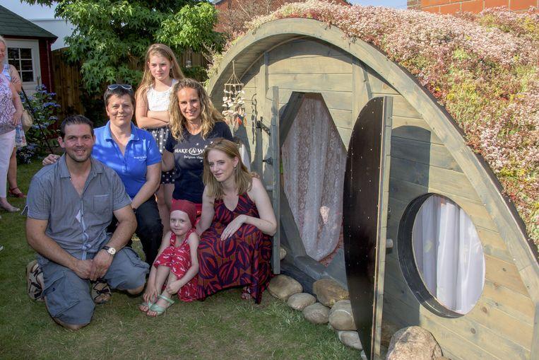 Fee met haar mama en papa en de mensen van Make-A-Wish aan het hobbithuisje.