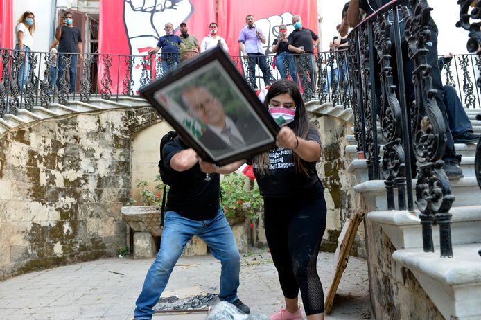 Demonstranten vernielen een foto van president Michel Aoun.