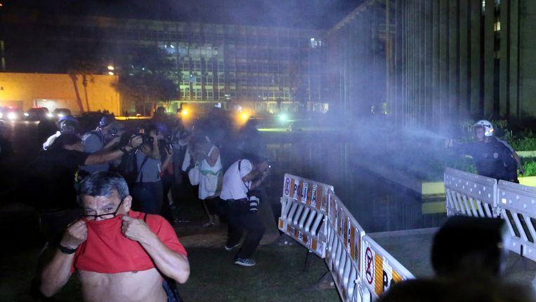 De politie gebruikt pepper spray in Brasilia.