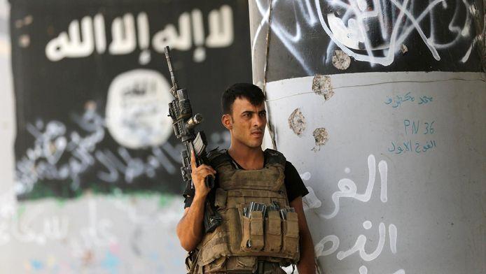 Soldat des forces irakiennes devant des symboles de l'EI à Fallujah(archives).