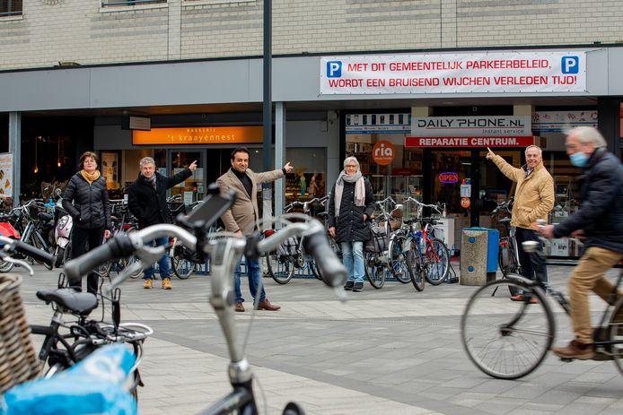 De ondernemers in Wijchen wijzen een spandoek aan waarin het parkeerbeleid wordt bekritiseerd.