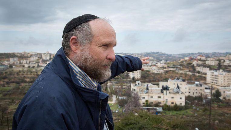 Hillel Manne, wijnhouder, laat zien hoe dichtbij de palestijnse huizen van de nederzetting vandaan staan. Beeld Cigdem Yuksel