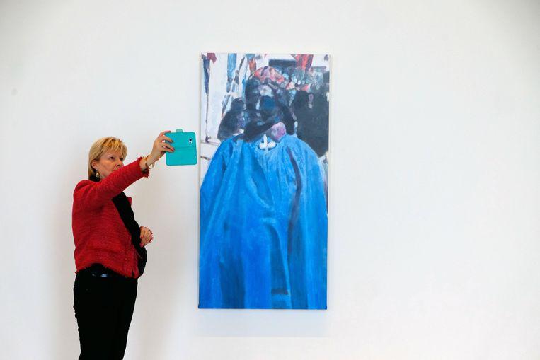 Een vrouw neemt een foto van het schilderij 'München' (2012). Beeld Photo News